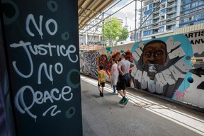 People walk past a mural of George Floyd in Graffiti Alley in Toronto on June 11, 2020. The well known Toronto alleyway is being painted with prominent black figures and messages of solidarity against anti-black racism in support of the Black Lives Matter movement.