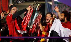 Liverpool manager Juergen Klopp, Adam Lallana and Mohamed Salah celebrate with the trophy after winning the Premier League last week.