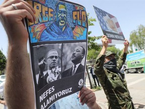 A protester holds a placard bearing the images of George Floyd, Malcom X and Martin Luther King on June 8, 2020, in Ankara, during a demonstration against racism and police brutality, and in solidarity with the Black Lives Matter movement, in the wake of the death of George Floyd, an unarmed black man killed while apprehended by police in Minneapolis, US.