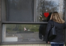 Diane Colangelo, daughter, looks through the window as Patricia Crump, 86,  lies on a bed inside Pickering's Orchard Villa long-term care home on Tuesday May 5, 2020.