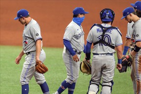 Blue Jays manager Charlie Montoyo (centre) removes pitcher Sam Gaviglio (left) from the game in the eighth inning on Saturday at Tropicana Field.