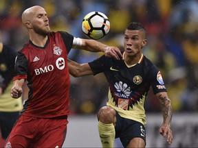 Toronto FC's Michael Bradley (left) battles for possession of the ball with Club America's Mateus Uribe during the second leg of their Concacaf Champions League semifinal on April 10, 2018, at Azteca Stadium in Mexico City.