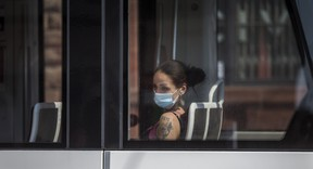 A TTC streetcar rider wears a mask along Queen St. E,  near Broadview Ave.  in Toronto on Thursday, July 2, 2020.