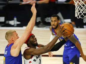 Terence Davis of the Toronto Raptors drives the ball against Mason Plumlee of the Denver Nuggets during the third quarter at The Field House at ESPN Wide World Of Sports Complex.