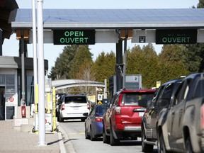 Drivers wait to cross through Canadian customs at the Canada-U.S. border near the Peace Arch Provincial Park in Surrey, B.C., March 16, 2020.