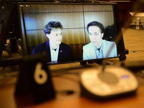 Marc Kielburger, screen left, and Craig Kielburger, screen right, appear as witnesses via videoconference during a House of Commons finance committee in the Wellington Building in Ottawa on Tuesday, July 28, 2020.