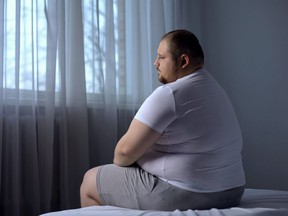 Depressed fat man sitting on bed at home, worried about overweight, insecurities
