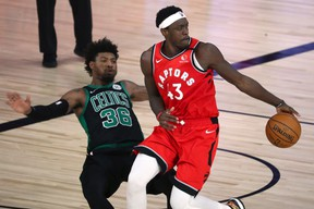 Raptors forward Pascal Siakam is defended by Celtics guard Marcus Smart during Monday night's game.
