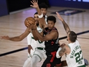 Kyle Lowry, centre, of the Toronto Raptors passes the ball as Daniel Theis, right, of the Boston Celtics defends during the third quarter in Game 4 of the Eastern Conference Second Round during the 2020 NBA Playoffs at the Field House at the ESPN Wide World Of Sports Complex on Sept. 5, 2020 in Lake Buena Vista, Fla.