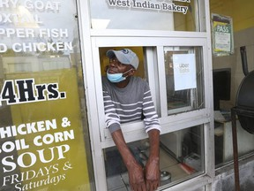 Ivoran Anson looks up at a bullet hole from the takeout window at a Spence's Bakery West Indian restaurant on Sept. 2, 2020 where six people were wounded hours earlier.