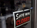 A closed sign is seen in the window of a small business.