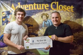 OLG lottery winner Shawn Farewell  and his son Ryan pose with Farewell's children's book artwork at their home in Aurora, Ont.