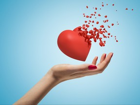 Close-up of woman's hand facing up and levitating red valentine heart that has started to disintegrate into pieces on light-blue background.
