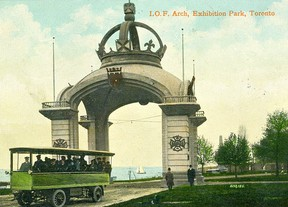 """To celebrate the visit to Canada and Toronto, known far and wide as the """"Queen City"""" by the Duke and Duchess of Cornwall and York (he was Queen Victoria's eldest son and soon to become King George V, his wife was to become Queen Mary), in the fall of 1901 various organizations erected large ceremonial arches in the cities to be visited by the Royal couple. The structure shown in this postcard was constructed out of wood and papier-mâché by the fraternal organization known as the Independent Order of Foresters. It was erected adjacent to the IOF's headquarters (reputed to be Toronto's first skyscraper) where it straddled the Bay and Richmond Sts. intersection. Following the Royal festivities, the arch was dismantled and re-erected on the Exhibition Grounds as an attraction in time for the following year's fair. At other times of the year, tourists visited the impressive monument during city sightseeing tours provided by battery-powered coaches. The elements finally got to the structure and it was removed and scrapped."""