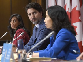Prime Minister Justin Trudeau and Minister of Public Services and Procurement Anita Anand listen to Chief Public Health Officer of Canada Dr. Theresa Tam during a news conference on the COVID-19 pandemic on Parliament Hill in Ottawa, on Friday, Sept. 25, 2020.