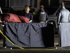 Investigators move the body of a man who is reportedly Michael Forest Reinoehl after he was shot and killed by law enforcement in Lacey, Washington on Sept. 3, 2020.