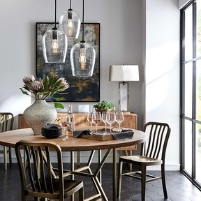 A modern dining space, lit from above, with taupe walls and a wooden table, sets a relaxing, rustic tone. Photo:  Crate and Barrel