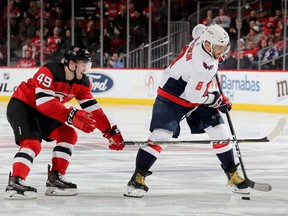 Alex Ovechkin #8 of the Washington Capitals takes the puck as Joey Anderson #49 of the New Jersey Devils defends in the third period at Prudential Center on March 19, 2019 in Newark, New Jersey.
