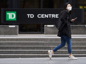 A woman in a mask walks in the financial district in Toronto, Ontario on March 24, 2020. - The province of Ontario has set a deadline of midnight Tuesday for all non-essential businesses to close due to the Covid-19 outbreak.