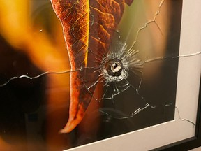 An image posted to Twitter by Lucas Timmons of damage to a photo after a bullet from a short-term rental unit next door entered his downtown condo Oct. 13, 2020.