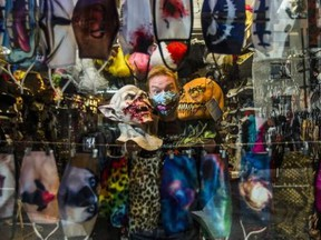 Geoff Waszek, owner of Candy's Costume Shop, 685 Mt. Pleasant Rd. is seen through the front window and hanging face masks at his store in Toronto, Ont. on Thursday October 15, 2020.