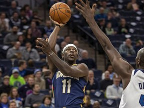 New Orleans Pelicans guard Jrue Holiday (11) shoots the ball over Minnesota Timberwolves center Gorgui Dieng (5) in the first half at Target Center.