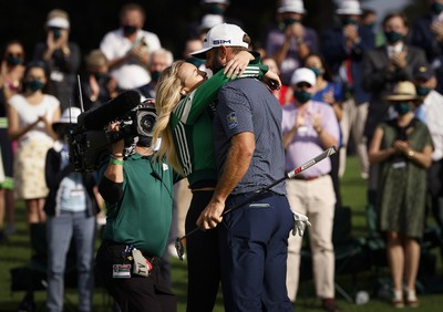 Dustin Johnson of the U.S. celebrates with his partner Paulina Gretzky on the 18th green after winning The Masters