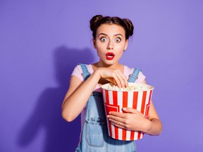 Close up photo beautiful amazing she her lady two buns watch tv show hold popcorn bucket eyes full fear mouth open wear casual t-shirt jeans denim overalls clothes isolated purple violet background