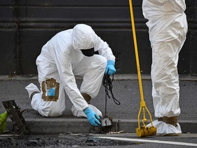 Police forensics officers conduct a search of a drain near to Forbury Gardens park in Reading, west of London, on June 22, 2020.