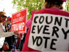 A counter-protester stands next to a woman holding a sign as supporters of U.S. President Donald Trump demonstrate near the Republican National Committee building after Election Day, in Washington, D.C., U.S., November 5, 2020.