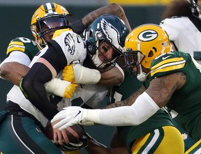 Carson Wentz #11 of the Philadelphia Eagles is sacked by Kingsley Keke #96 and Preston Smith #91 of the Green Bay Packers on Sunday. Wentz was benched in the Packers' win.