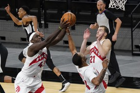 Raptors forward Pascal Siakam (43) grabs a rebound as guards Matt Thomas (21) and Norman Powell (24) look on during the second quarter against the Spurs in San Antonio on Saturday night.