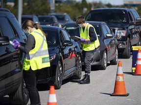 Paramedics register patients at a drive through, pop-up COVID-19 test centre outside the Canadian Tire Centre in Ottawa, Sunday, Sept. 20, 2020.