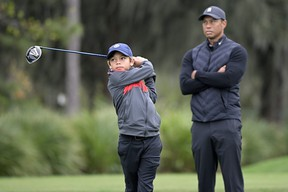 Tiger Woods watches as his son Charlie tees off on the 12th hole during a practice round for the PNC Championship in Orlando, Fla., on Thursday.