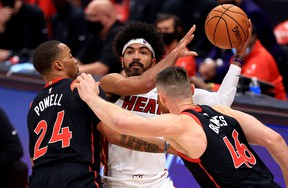 Miami Heat's Gabe Vincent is pressured by Raptors' Norman Powell and Aron Baynes during Friday's game.