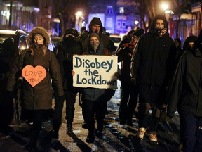 Protesters walk down streets as they ignore a night curfew imposed by the Quebec government to help slow the spread of the COVID-19 pandemic in Montreal, Jan. 9, 2021.