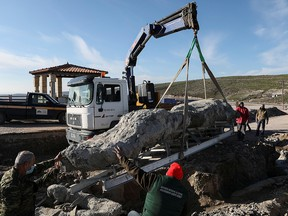 Workers lift a fossilized tree, part of a petrified forest, with a crane on the island of Lesbos, Greece, December 19, 2020.