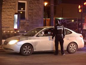 Police ticket a vehicle as they enforce a night curfew imposed by the Quebec government to help slow the spread of COVID-19, in Montreal, Saturday, Jan. 9, 2021.