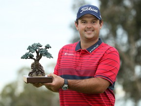 Patrick Reed celebrates with the trophy after winning the Farmers Insurance Open at Torrey Pines South on Jan. 31, 2021 in San Diego, Calif.