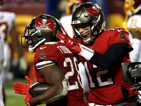 Buccaneers QB Tom Brady (right) congratulates running back Leonard Fournette (left) after a touchdown against Washington during NFL playoff action at FedExField in Landover, Md., Saturday, Jan. 9, 2021.