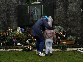 Denise Gormley and her daughter Rosa, 7, pay their respects at the Tuam graveyard, where the bodies of 796 babies were uncovered at the site of a former Catholic home for unmarried mothers and their children, on the day a government-ordered inquiry into former Church-run homes for unmarried mothers is formally published, in Tuam, Ireland, Tuesday, Jan. 12, 2021.