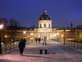 People walk on the Pont des Arts covered with snow, during a nationwide curfew, from 6 p.m. to 6 a.m., due to restrictions against the spread of the coronavirus disease (COVID-19), in Paris, France, January 16, 2021.