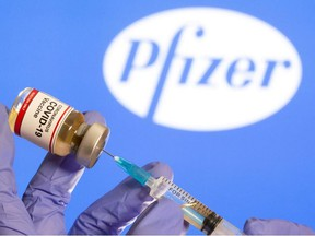 "A woman holds a small bottle labeled with a ""Coronavirus COVID-19 Vaccine"" sticker and a medical syringe in front of the displayed Pfizer logo in this illustration taken, October 30, 2020."