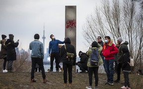 People gather around a steel monolith that has been placed at Humber Bay Park East in Toronto, Ont. on Friday, Jan. 1, 2021.