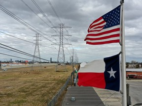 The U.S. and Texas flags fly in front of high voltage transmission towers on February 21, 2021 in Houston, Texas.