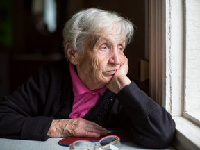 A depressed senior looks out the window