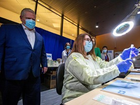 Ontario Premier Doug Ford watches a health-care worker prepare a Pfizer-BioNTech coronavirus disease (COVID-19) vaccine at The Michener Institute, in Toronto, on Jan. 4, 2021.