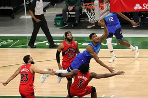 A number of Raptors, including DeAndre' Bembry (top) defend two-time NBA MVP Giannis Antetokounmpo.