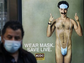 """A person wearing a mask walks past a bus stop ad on 5th Avenue, October 15, 2020, for the movie """"Borat 2,"""" featuring actor Sacha Baron Cohen, ahead of its release on October 23."""