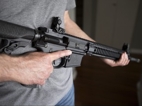 A restricted gun licence holder holds a AR-15 at his home in Langley, B.C. on May 1, 2020.